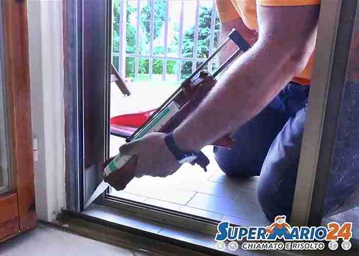 Tecnico ripara con silicone la chiusura di un infisso della finestra